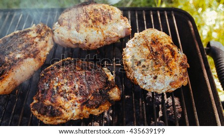 Grilling steaks on flaming grill. Cooking food meat on grill on flame. Beef burgers on bbq barbecue grill with flame. Preparing grilling steaks on barbecue grill. Classic BBQ meat meal. - stock photo