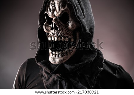 Grim reaper on a dark background, halloween background. - stock photo