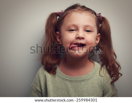 Grimacing beautiful little girl showing the tongue. Closeup vintage portrait - stock photo