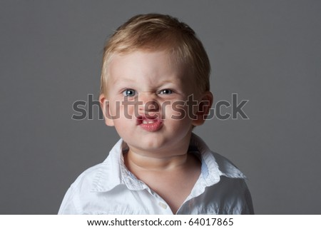 grimacing boy - stock photo