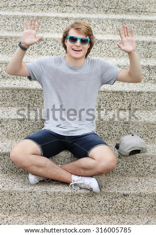 Grimacing.Laughing teenage boy doing hand sign - stock photo