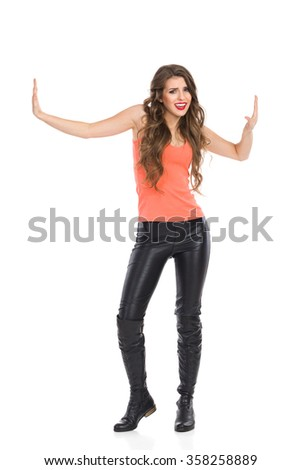 Grimacing woman standing with arms outstretched and pressing fake walls. Full length studio shot isolated on white.