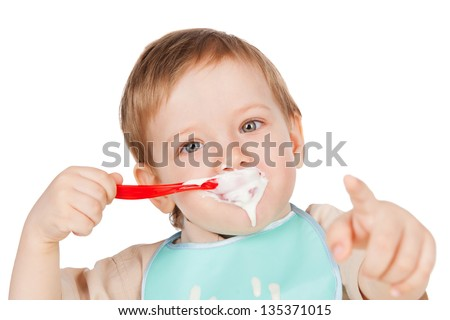 Grimy boy eats with a spoon sour cream - stock photo