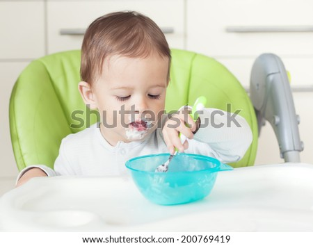grimy funny child eats sour cream in the chair. small depth of field (DOF) - stock photo