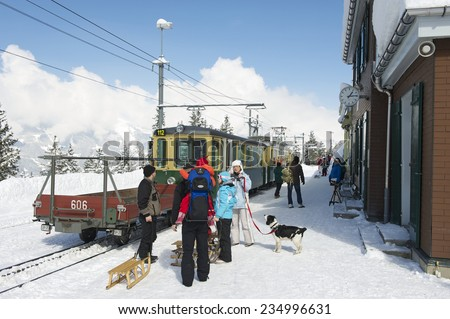 GRINDELWALD, SWITZERLAND - MARCH 07, 2009: Unidentified tourists wait for a train at Wengernalpbahn train station in Grindelwald, Switzerland. Grindelwald area is a famous ski resort in Switzerland. - stock photo