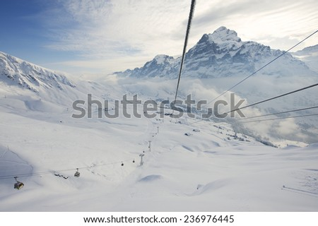 GRINDELWALD, SWITZERLAND - MARCH 07, 2009: View from the gondola to the cable car moving and ski resort on March 07, 2009 in Grindelwald, Switzerland.  - stock photo