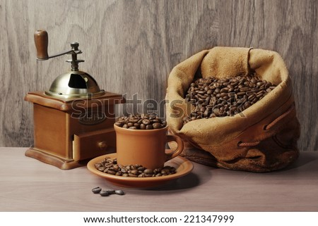Grinder, cup of coffee with beans and grains sack - stock photo