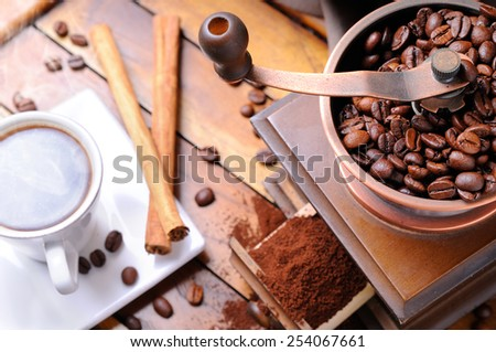 Grinder with coffee beans on a wooden table with cup brown top view - stock photo