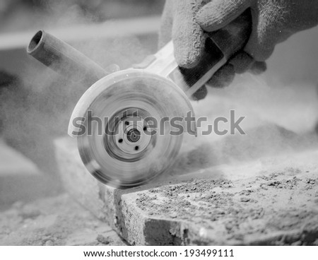 grinder worker cuts a stone the electric tool - stock photo