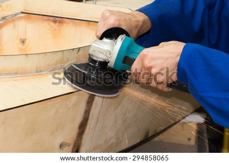 Grinding the wooden boat by cutting grinder process - stock photo
