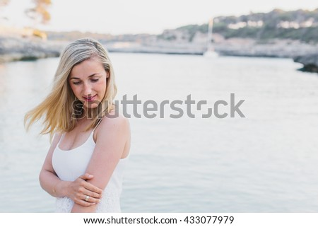 Grinning blond woman in sleeveless white dress holding her arm while standing near edge of water with copy space to the side - stock photo