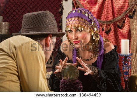 Grinning European fortune teller with hands over crystal ball - stock photo