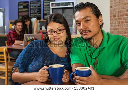 Grinning Latino and Asian couple in cafe
