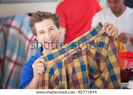 Grinning man holds a plaided shirt in laundromat - stock photo