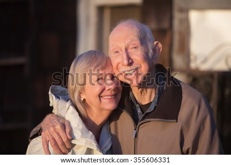 Grinning older couple embracing while standing outdoors - stock photo