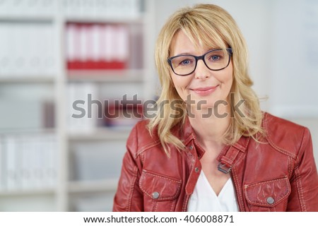 Grinning single mature woman in red leather jacket, blond hair and eyeglasses with cheerful expression in office with shelf in background