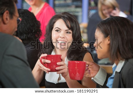 Grinning woman and coworkers with coffee in bistro - stock photo