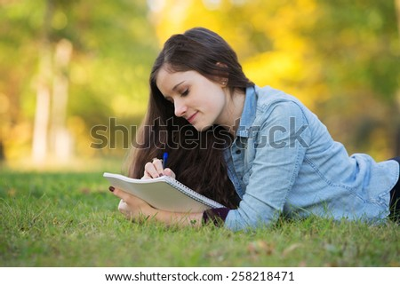 Grinning young woman writing on notebook outdoors - stock photo