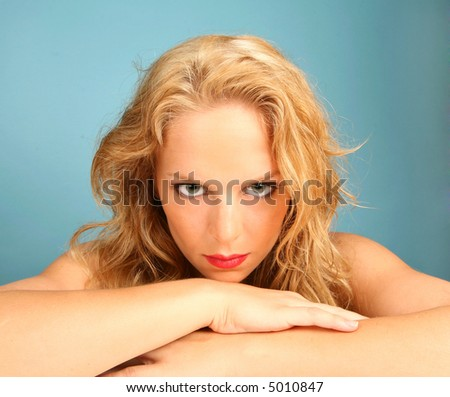 Gripping Stare of a Beautiful Woman on Blue Background - stock photo