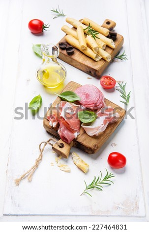 Grissini bread sticks, prosciutto ham, pancetta, salami, olive oil, basil on old wooden background - stock photo