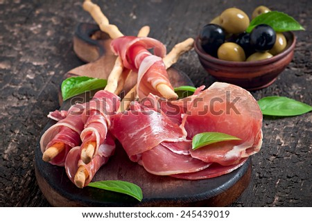Grissini bread sticks with ham, olives, basil on old wooden background - stock photo