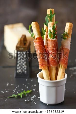 Grissini bread sticks with prosciutto ham, arugula and parmesan cheese. - stock photo
