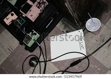 Gritty images of blank set list on stage with guitar effect pedals and instrument cables