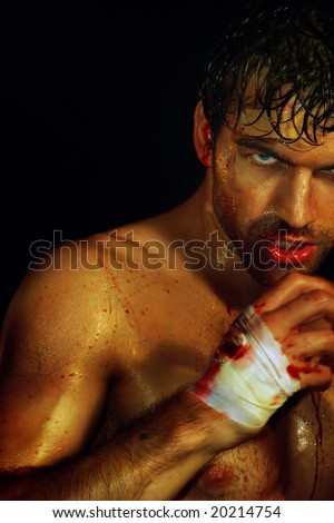 Gritty portrait of a sexy, sweaty, young, bloody boxer ready to fight