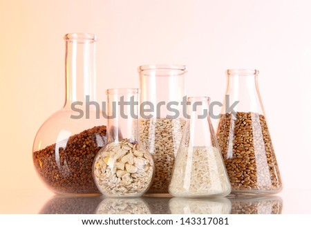 Groats in test tubes on orange background - stock photo