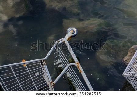 Grocer store shopping cart sits in clear water after being taken away by flooding - stock photo
