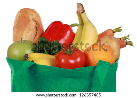 Groceries in a bag including a bread, fruits and vegetables, isolated on white - stock photo