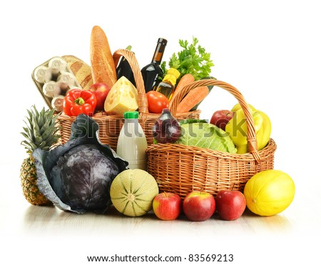 Groceries in wicker basket consisting of vegetables, fruits, dairy and bakery products isolated on white - stock photo