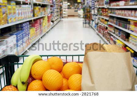 Grocery cart loaded with fresh fruit and bread moving through the aisle. - stock photo