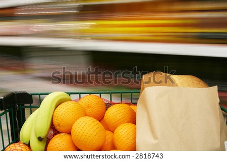 Grocery cart loaded with fresh fruit and bread, rushing through the store. - stock photo