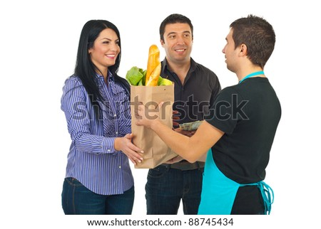 Grocery clerk man giving paper bag with food to couple isolated on white background - stock photo