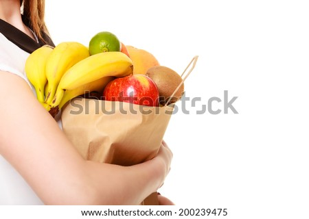 Grocery shop. Recycling paper shopping bag with fresh fruits in hands of client woman girl isolated on white. Healthy food. - stock photo