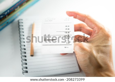 Grocery shopping list in hand - money account management concept - stock photo