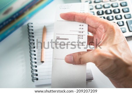 Grocery shopping list in hand with calculator and pencil - money account management concept - stock photo