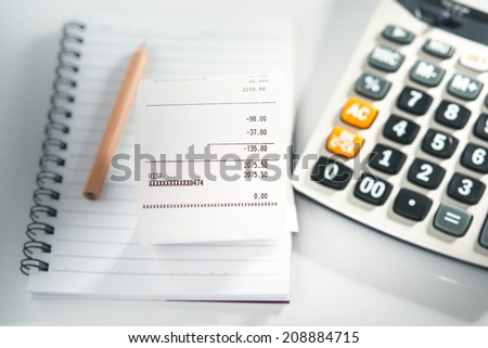 Grocery shopping list on notebook with calculator and pencil - money account management concept - stock photo
