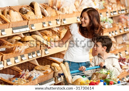 Grocery store - Brown hair woman with child buying bread - stock photo