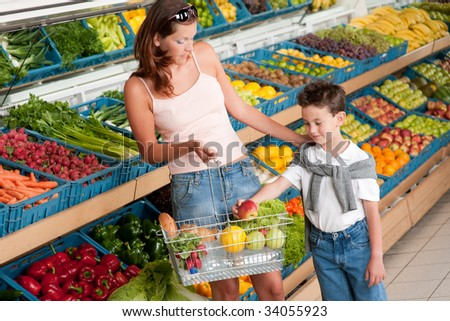 Grocery store - Mother with child buying fruit in a supermarket - stock photo