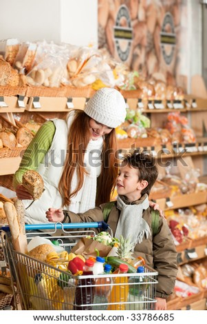 Grocery store - Red hair woman with child in a supermarket - stock photo