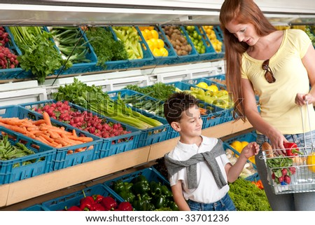 Grocery store - Red hair woman with child in grocery store - stock photo