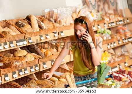 Grocery store: Red hair woman with mobile phone and shopping cart - stock photo