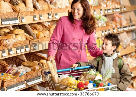 Grocery store - Smiling woman with child in a supermarket - stock photo