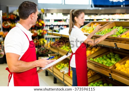 Grocery store staff with clipboard in grocery store - stock photo