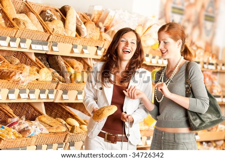 Grocery store: Two women choosing bread and having fun - stock photo