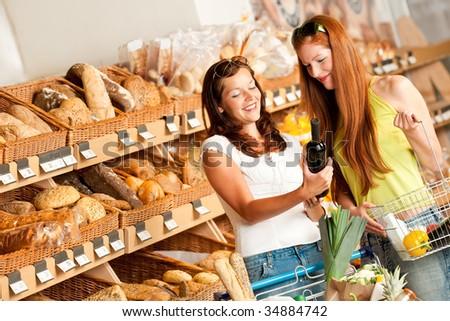 Grocery store: Two women choosing wine in a supermarket - stock photo