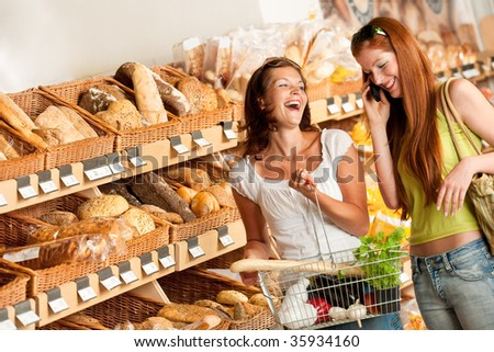 Grocery store: Two women having fun while shopping - stock photo