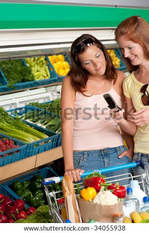 Grocery store - Two women with mobile phone in a grocery store - stock photo
